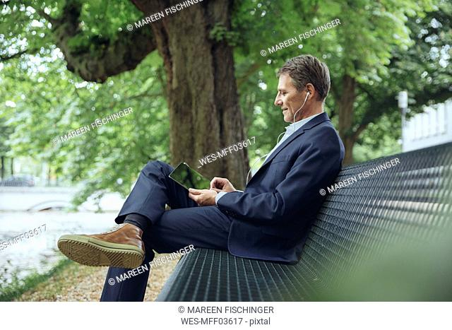 Smiling mature businessman sitting on park bench with tablet and earphones