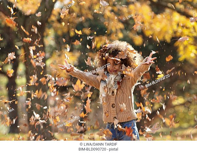 Black girl throwing autumn leaves