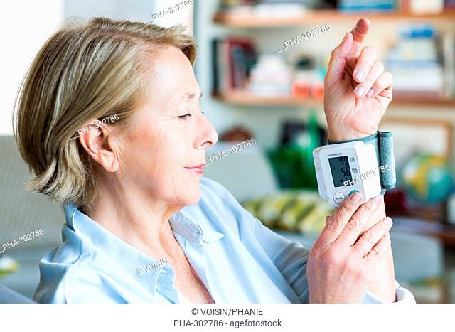 Woman taking her blood pressure with a portable blood pressure monitor