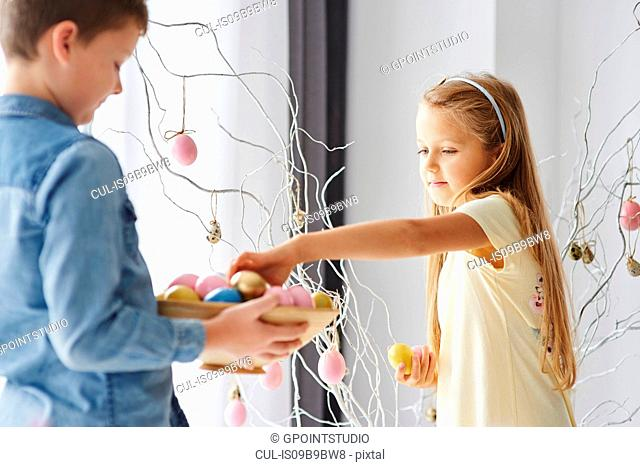 Girl and brother decorating twigs with colourful easter eggs