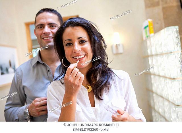 Hispanic couple getting ready in bathroom