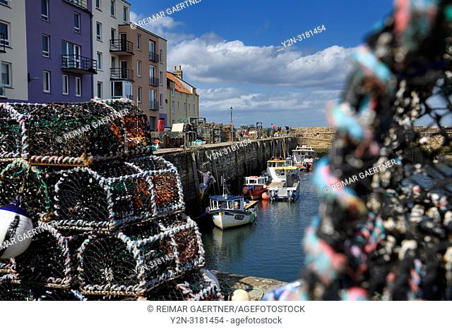 Lobster traps and working fisherman with fishing boats moored at St Andrews Pier Kinness Burn St Andrews Fife Scotland UK