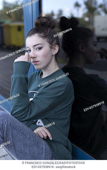 Teen girl sitting looking towards the camera. Vertical shot with natural light