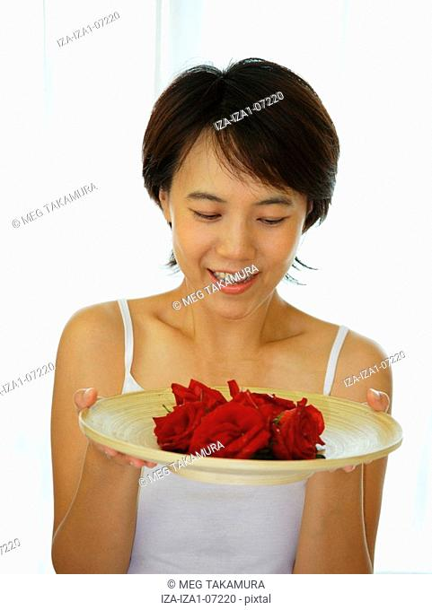 Close-up of a young woman holding a plate of Roses