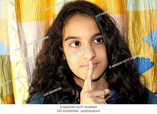 Silence please. Indian girl is making silence gesture