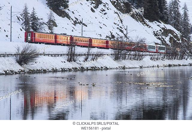 Bernina Red Train reflected in the river at Celerina in Engadin - Switzerland during winter