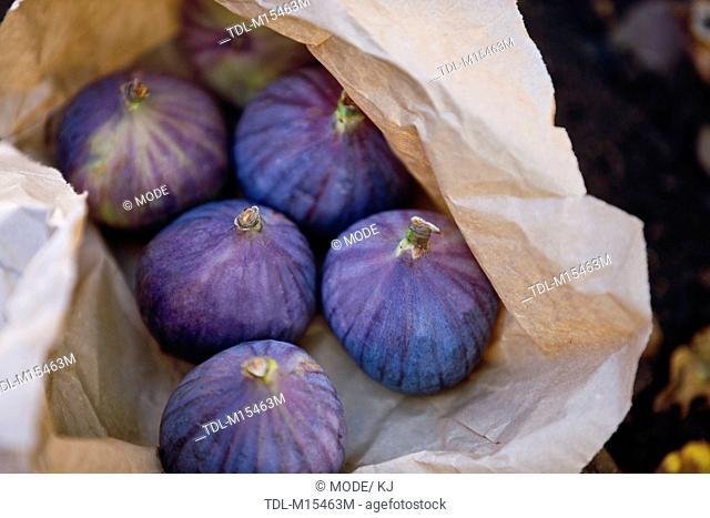 Six ripe figs in a brown paper bag