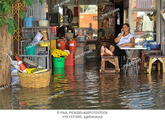 chinese lady talking on mobile phone whilst her shop is flooded, bangkok floodings, chinatown, bangkok, thailand