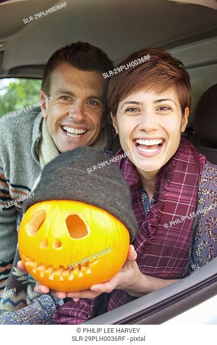 Man and woman with pumpkin on Halloween