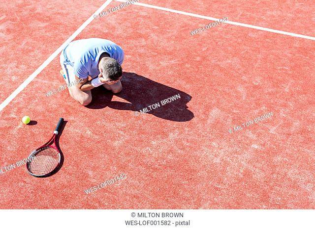 Tennis player with hands on head crouching on tennis court
