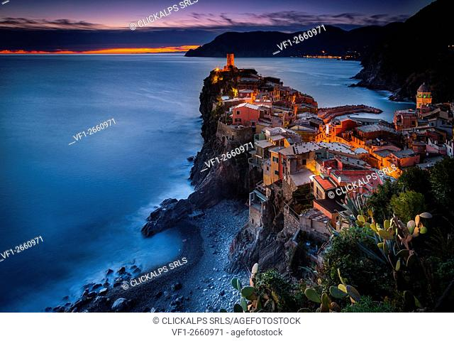 Vernazza, Liguria, Italy. View of the village during sunset, with trees on the foreground and the sea on the background
