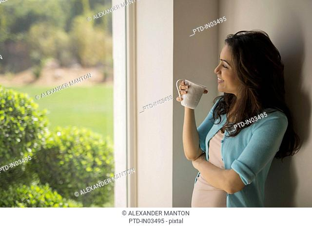 India, Woman standing at window with coffee cup