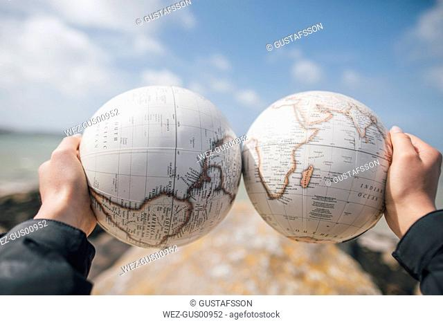 France, Brittany, Landeda, hands holding parts of a globe at the coast