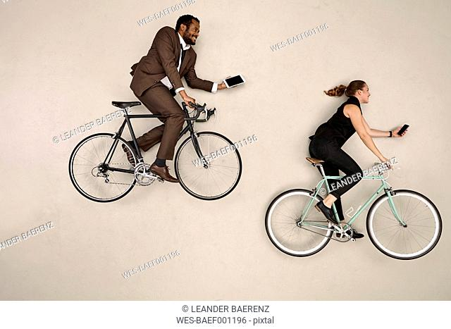 Two business colleagues biking with smartphone and tablet