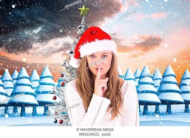 Woman in santa hat with finger on lips against digitally generated background