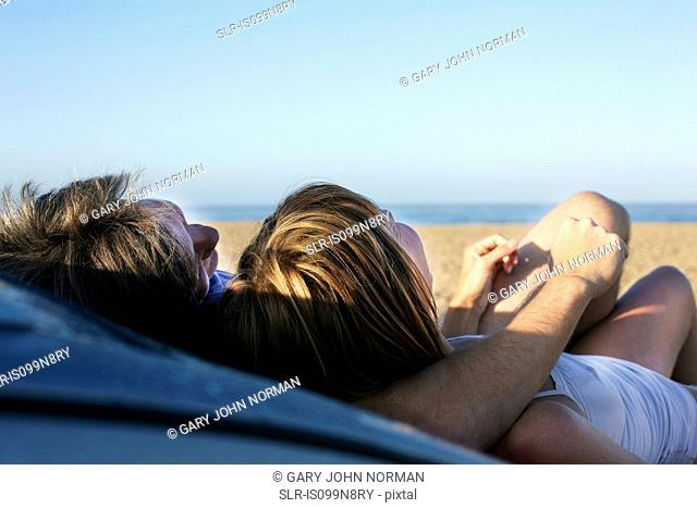 Mid adult couple relaxing on car on beach