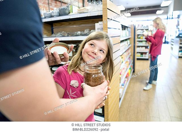 Father and daughter smelling jar in nutrition store