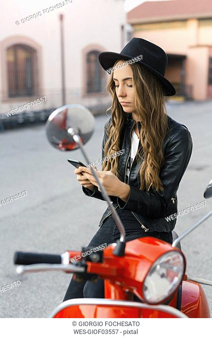 Portrait of fashionable young woman with red motor scooter using cell phone
