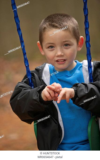 Boy signing the word Swing in American Sign Language on a swing