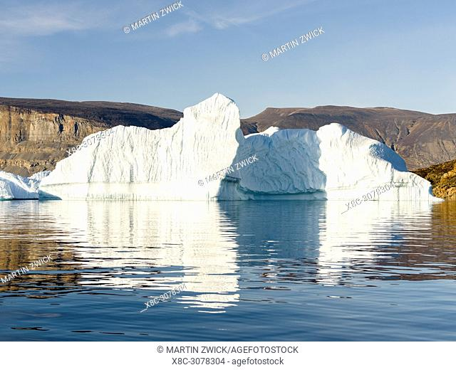 Landscape with steep yellow cliffs and icebergs in the Uummannaq fjord system in the north of west greenland. America, North America, Greenland, Denmark
