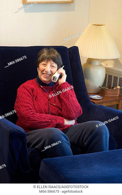 Seventy-four year old woman sitting in a living room chair talking on a portable phone in her New York home