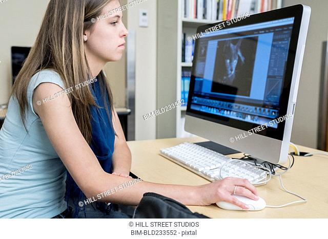 Caucasian girl using computer in photography class
