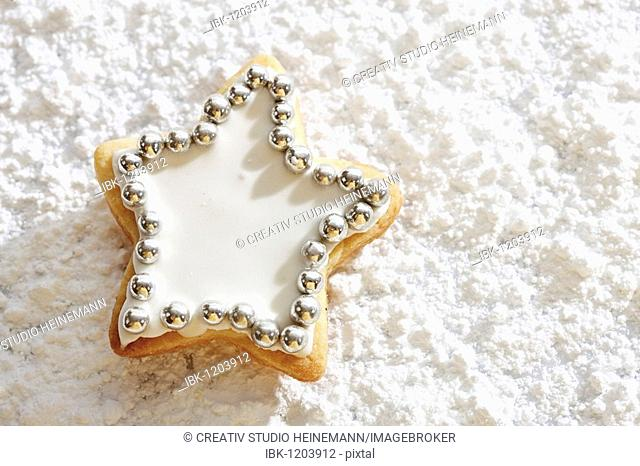 Star-shaped short pastry cookies, covered with sugar coating and silver sugar pearls, on icing sugar