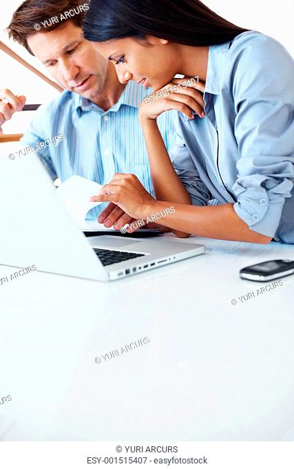 Successful businesswoman discussing while working on laptop with colleague