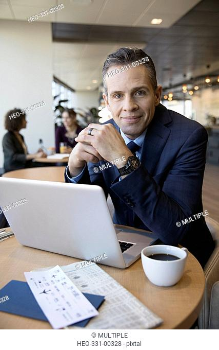 Portrait confident businessman working and drinking coffee at laptop in airport lounge