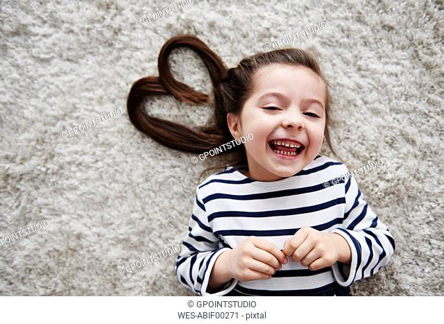 Portrait of laughing little girl lying on carpet