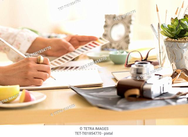 Young woman writing in note pad