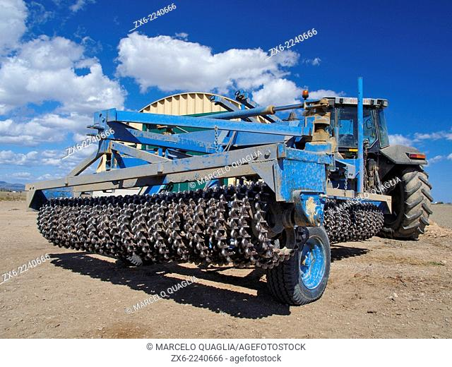 Tractor with special plough for turning over rice field soil. Ebro River Delta Natural Park, Tarragona province, Catalonia, Spain