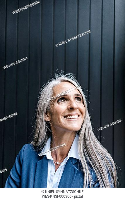 Portrait of smiling woman with long grey hair looking up