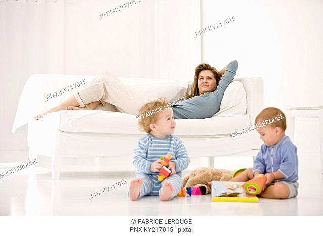 Babies playing with toys and their mother resting on a couch