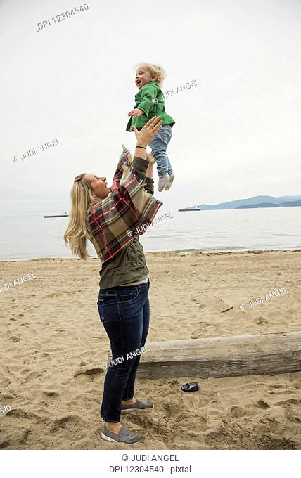 In a winter beach scene, a mother joyfully throws her little girl in the air; Vancouver, British Columbia, Canada