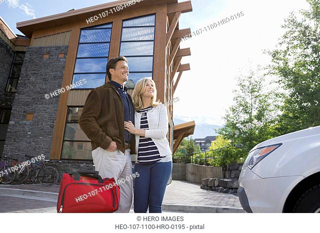 Couple with luggage outside hotel