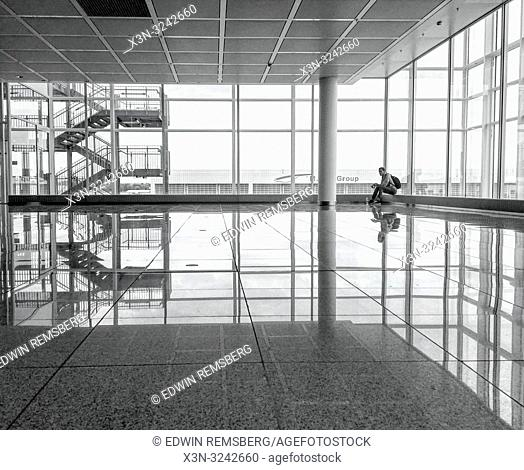 Man sits alone in terminal at Munich airport with large windows reflecting light onto shiny floor, MŸnchen, Germany