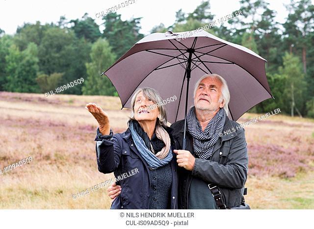 Senior couple under umbrella checking for rain
