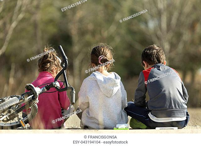 Three children sitting on the floor with their backs to the camera taking their snack. Horizontal shot with natural light