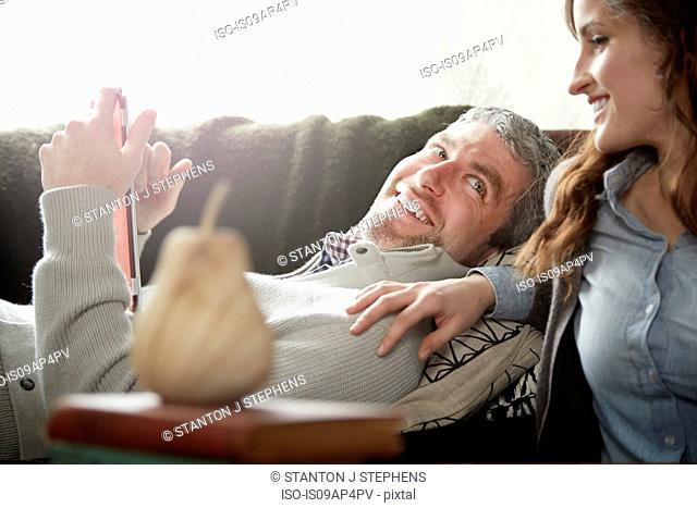Young couple in sitting room browsing digital tablet