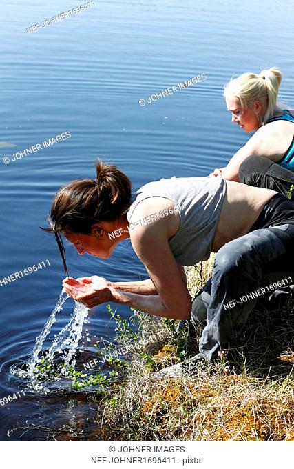 Women drinking water from lake