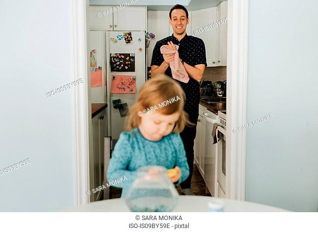 Female toddler at table and father in kitchen