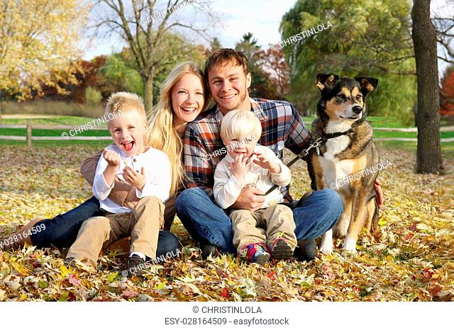A portrait of a happy family of four people, including mother, father, little boy, and toddler brother, are sitting outside in the fallen leaves with their pet...