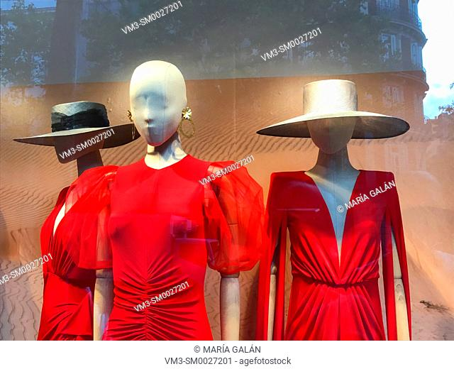 Three mannequins wearing red dresses in a shop window. Madrid, Spain