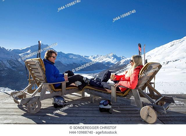 Couple in deck chairs in mountain restaurant Trutz, Engadine, Grisons