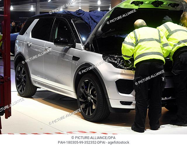 05 March 2018, Switzerland, Geneva: People work on a Land Rover at a fair stand on the previous day of the Geneva Motor Show's press days
