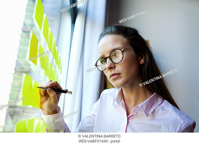Businesswoman writing on post it at glass pane