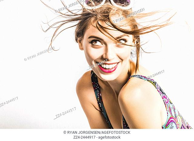Studio salon portrait on the face of a beautiful brunette girl with short reddish brown hair fluttering in a windy breeze