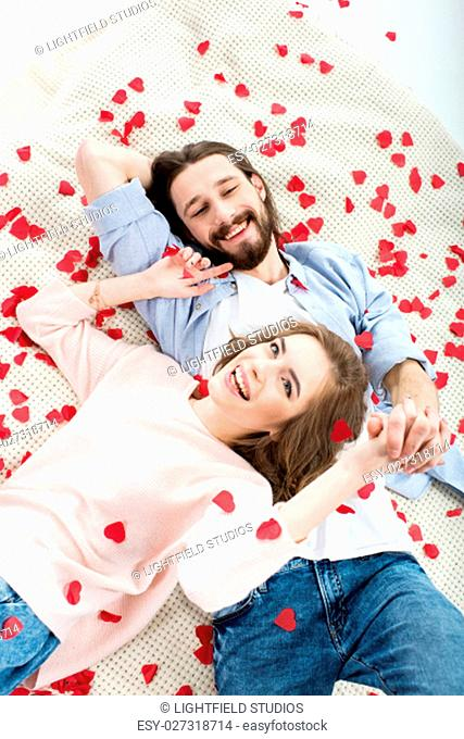 Beautiful young couple in love lying together and smiling on red paper hearts