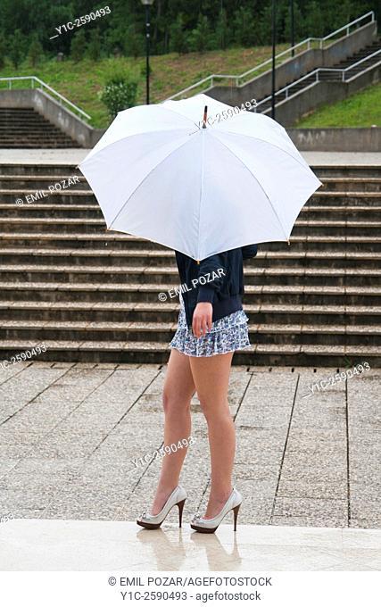 Young woman under White umbrella walking on wet ground